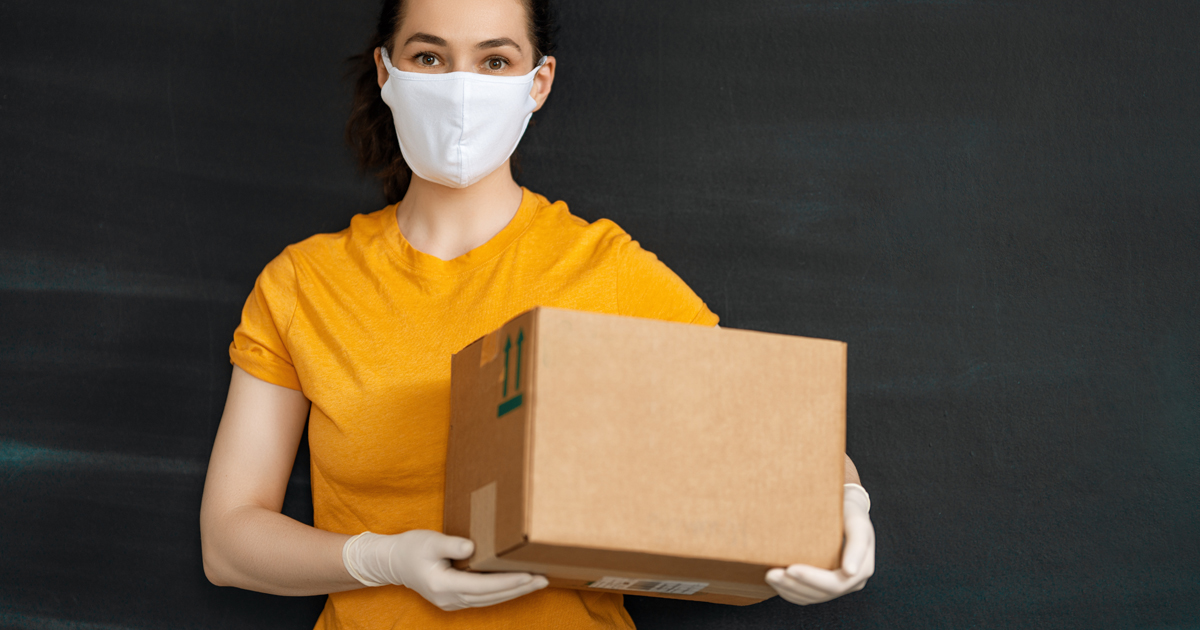 Masked woman carrying a delivery